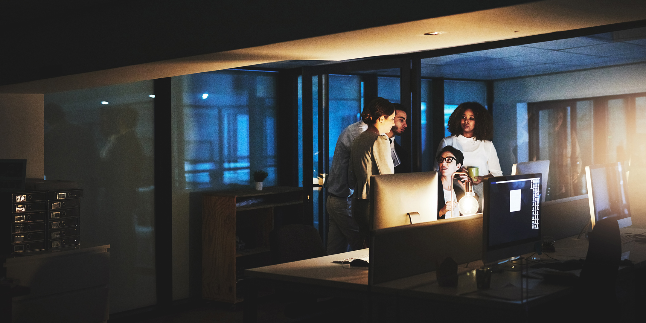 Security professionals gathered around a computer at night.